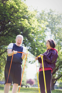 Enthusiastic active senior couple exercising, using resistance bands in sunny parkの写真素材 [FYI02190501]