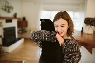 Affectionate girl holding black catの写真素材 [FYI02190502]