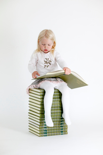 Girl (4-5) sitting on stack of books and reading one of themの写真素材 [FYI02190515]