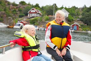Sweden, Bohuslan, Tjorn, Mother with daughter (3-4) in motorの写真素材 [FYI02190587]