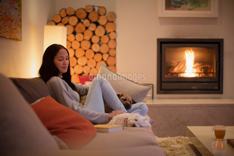 Young woman relaxing on sofa with dogs by fireplaceの写真素材 [FYI02190608]