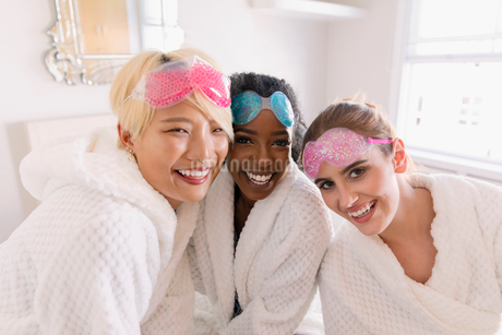 Portrait happy young women friends in bathrobes and eye masksの写真素材 [FYI02190643]