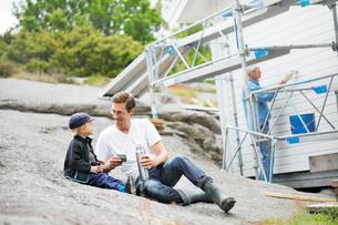 Sweden, Bohuslan, Mid adult man drinking with boy (4-5) formの写真素材 [FYI02190647]