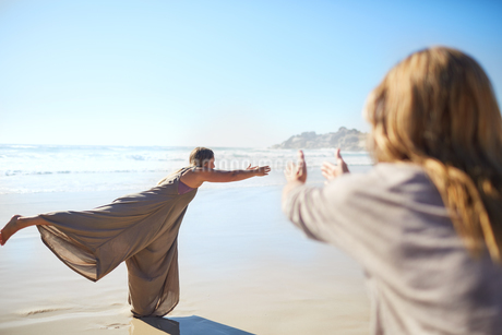 Woman practicing warrior 3 pose on sunny beach during yoga retreatの写真素材 [FYI02190694]