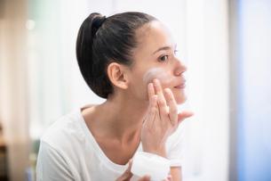 Woman applying moisturizer to face in bathroom mirrorの写真素材 [FYI02190772]