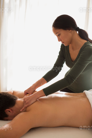 Female masseuse giving man massageの写真素材 [FYI02190837]