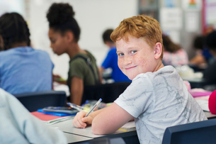 Portrait smiling, confident junior high school boy student studying at desk in classroomの写真素材 [FYI02190863]