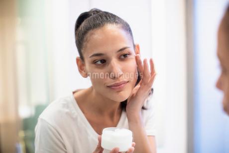Woman applying moisturizer to face in bathroom mirrorの写真素材 [FYI02190874]