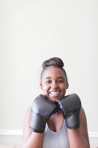 Portrait confident teenage girl wearing boxing glovesの写真素材 [FYI02190885]