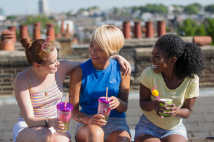 Young women friends bonding, drinking on sunny summer rooftopの写真素材 [FYI02190888]