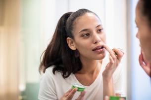 Woman applying lip balm in mirrorの写真素材 [FYI02190906]