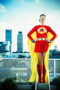 Superhero standing on stepladder on city rooftopの写真素材 [FYI02190939]