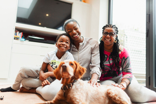 Portrait happy multi-generation family with dog on living room floorの写真素材 [FYI02190961]