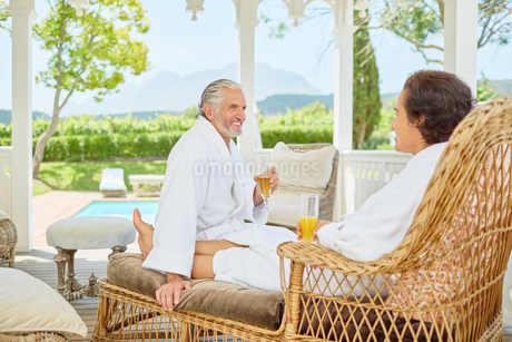 Mature couple in bathrobes relaxing, drinking mimosas in resort gazeboの写真素材 [FYI02190968]