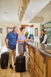 Mature couple with suitcases checking in at hotel receptionの写真素材 [FYI02190975]