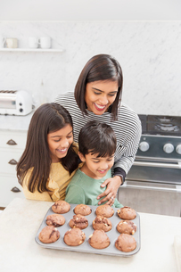 Mother and children baking chocolate muffins in kitchenの写真素材 [FYI02191022]