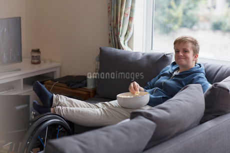 Portrait confident young woman watching TV and eating popcorn on sofa with feet up on wheelchairの写真素材 [FYI02191043]