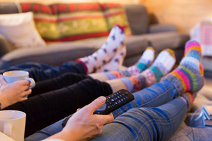 Family in colorful socks relaxing, watching TV in living roomの写真素材 [FYI02191050]