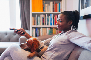 Young woman and dog relaxing, watching TV on living room sofaの写真素材 [FYI02191116]