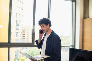 Man using laptop and talking on smart phone at urban apartment windowの写真素材 [FYI02191154]