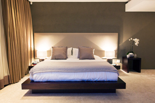 Modern bedroom with double bed illuminated at nightの写真素材 [FYI02191289]