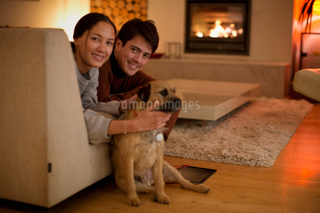 Portrait happy couple with dog in living roomの写真素材 [FYI02191333]