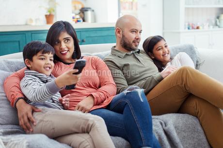 Family watching TV on living room sofaの写真素材 [FYI02191335]