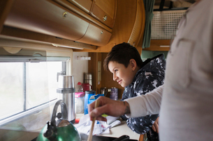 Father and soon cooking and looking out window in motor homeの写真素材 [FYI02191410]