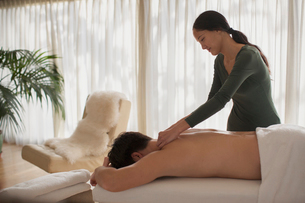 Female masseuse giving man massageの写真素材 [FYI02191449]