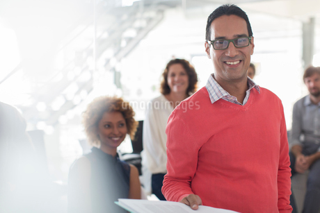 Portrait of smiling businessman wearing glasses and pink sweatshirt with team in backgroundの写真素材 [FYI02191458]
