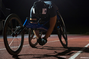 Tired paraplegic athlete resting on sports track after wheelchair race at nightの写真素材 [FYI02191528]