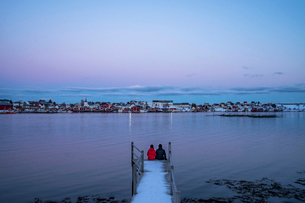Couple sitting at the edge of snowy pier overlooking waterfront fishing village, Reine, Lofoten Islaの写真素材 [FYI02191551]