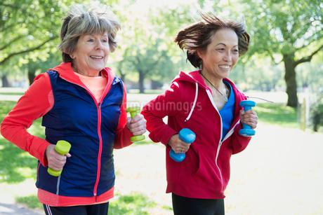 Active senior women friends jogging with hand weights in parkの写真素材 [FYI02191552]