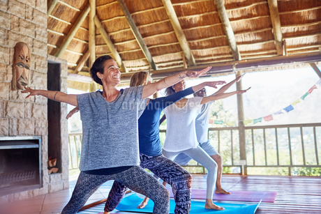 Happy woman practicing yoga warrior 2 pose in hut during yoga retreatの写真素材 [FYI02191553]