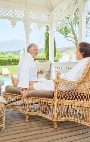 Mature couple in bathrobes relaxing, drinking champagne in resort gazeboの写真素材 [FYI02191565]