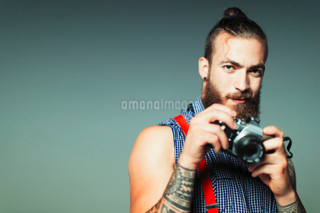 Portrait hipster man with retro cameraの写真素材 [FYI02191571]