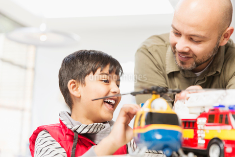 Father and son playing with helicopter and fire engine toysの写真素材 [FYI02191616]