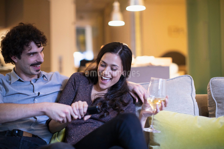 Playful couple fighting over the remote control, watching TV and drinking white wine on sofaの写真素材 [FYI02191624]