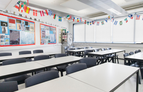 International flags hanging over desks in classroomの写真素材 [FYI02191656]