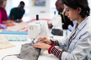 Focused female fashion designer using sewing machineの写真素材 [FYI02191663]