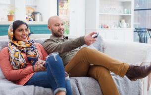 Couple watching TV on living room sofaの写真素材 [FYI02191665]