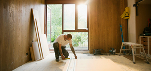 Construction worker measuring wood board in houseの写真素材 [FYI02191680]