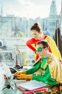 Superheroes working on laptop in officeの写真素材 [FYI02191706]