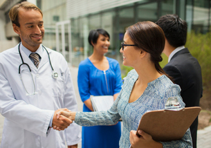 Smiling doctor shaking hand with woman in front of hospitalの写真素材 [FYI02191784]