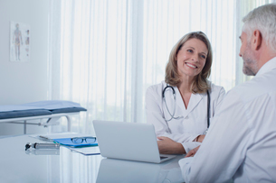 Smiling female doctor talking to patient at desk in officeの写真素材 [FYI02191788]