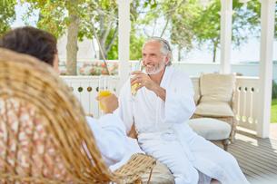Mature couple in spa bathrobes drinking mimosas in resort gazeboの写真素材 [FYI02191795]