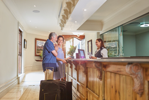 Mature couple with suitcases checking in at hotel receptionの写真素材 [FYI02191798]