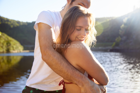 Affectionate couple hugging at sunny summer lakeの写真素材 [FYI02191808]