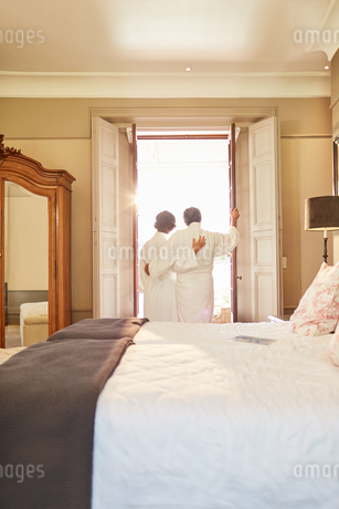 Affectionate couple in spa bathrobes standing at hotel balcony doorwayの写真素材 [FYI02191842]