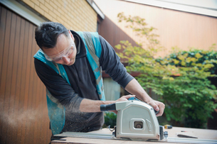 Construction worker using table saw in drivewayの写真素材 [FYI02191875]